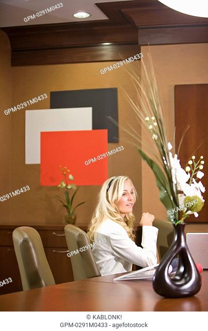Portrait of young fashionable businesswoman at meeting table in modern office