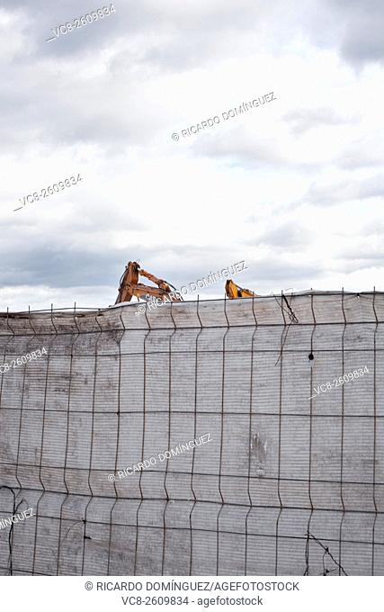 Digger machines working behind a covered fence