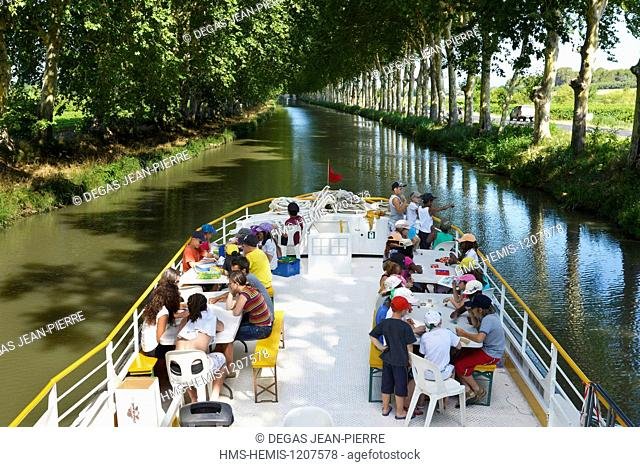 France, Herault, Cers, Canal du Midi listed as World Heritage by UNESCO, children on a barge in the middle of a stream in the shade of plane trees