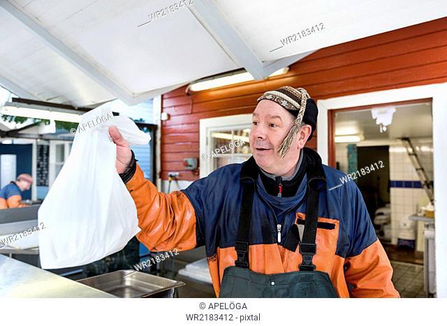 Mature fisherman giving plastic bag of fish at fishing industry