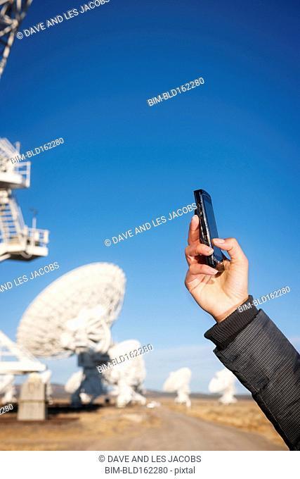 Hispanic woman taking cell phone photograph of satellite