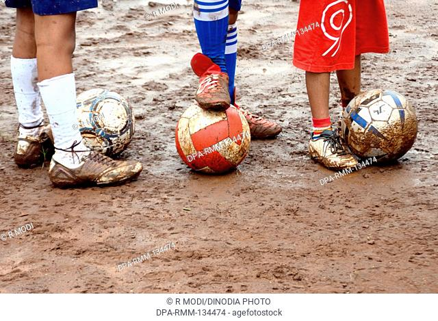 South Asian Indian boys playing , practice , enjoying with foot ball during monsoon season , India NO MR