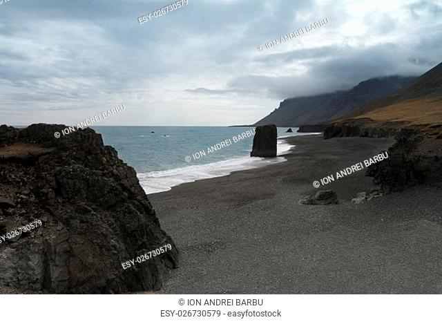 Horizontal view of an Icelandic beach with a huge rock formation in the middle