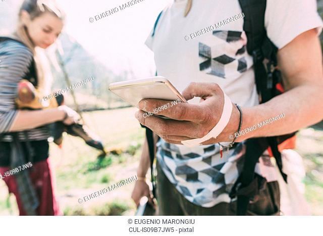 Hand of male boulderer holding smartphone, Lombardy, Italy