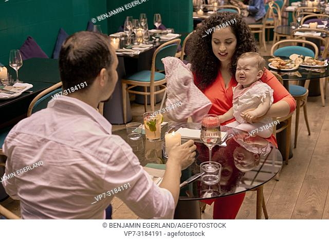 couple with baby eating in restaurant, Vegan Oriental, Kismet, in Munich, Germany