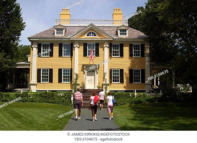 A family walks up to the front door of the Longfellow House, a historic site in Cambridge, Massachusetts