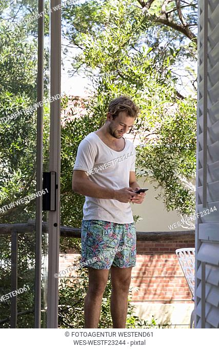 Young man in swimming trunks and t-shirt using cell phone