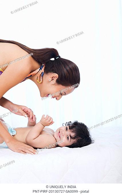Woman playing with her son on the bed