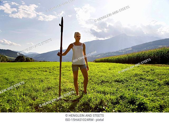 girl standing in pasture with scythe