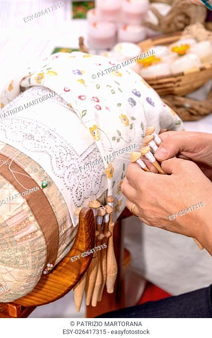 Woman hands embroider bobbin lace, lace carefully