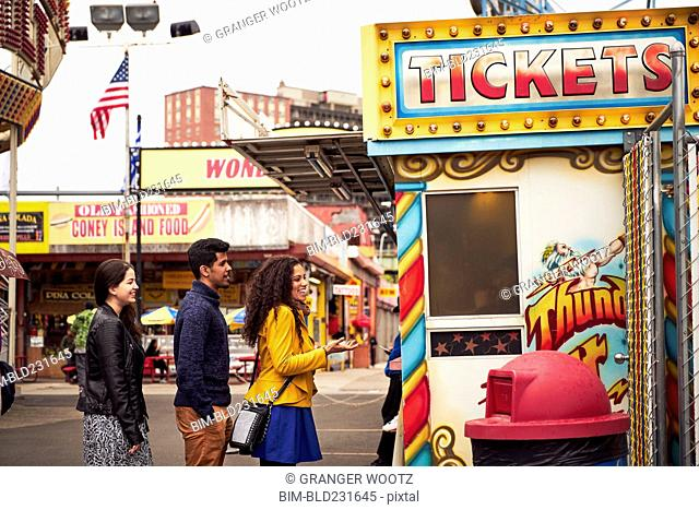 Friends waiting in line at amusement park ticket booth