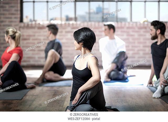 Yoga class doing exercise in studio
