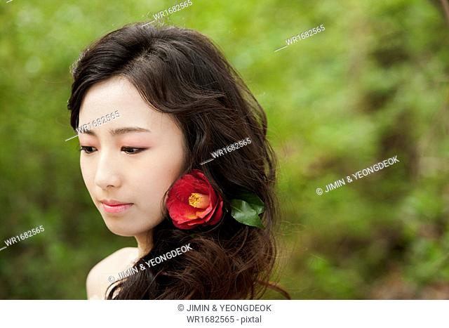 a woman with a flower posing in the nature