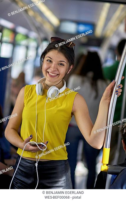 Portrait of smiling young woman with cell phone and headphones in underground train