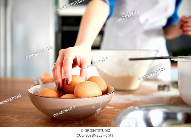 Woman taking egg from bowl in kitchen
