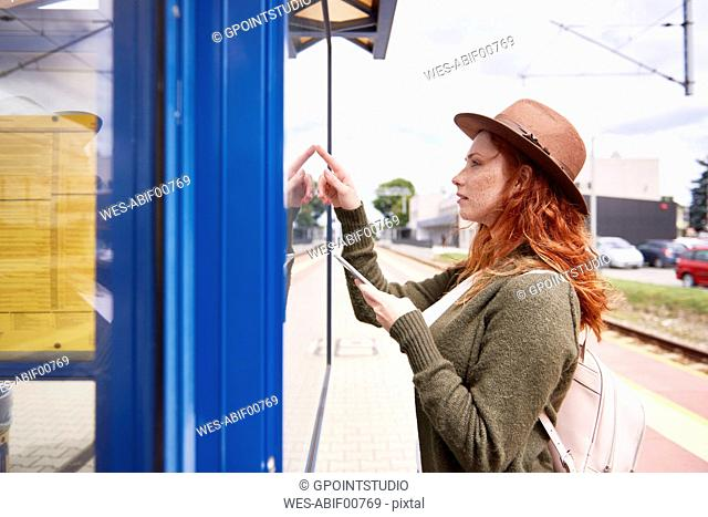 Redheaded young woman looking at timetable on platform
