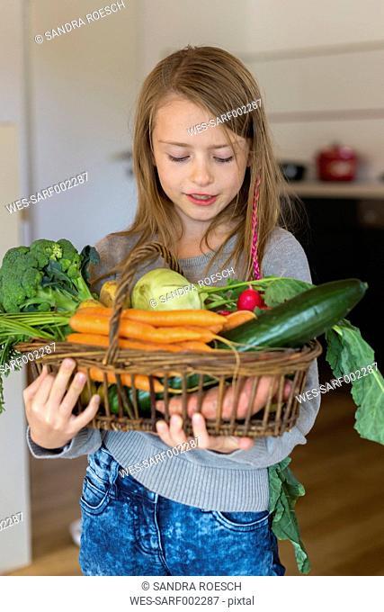 Portrait of girl holding wickerbasket of fresh vegetables