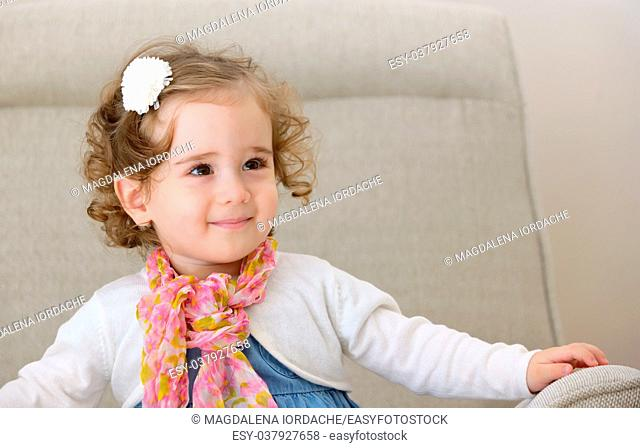Happy little girl sitting on armchair