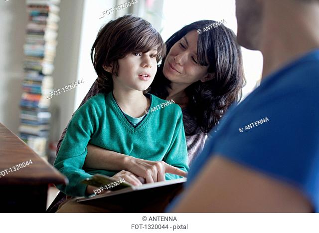 Mother explaining to son while reading book