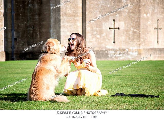 Woman posing with cup of tea and golden retriever dog at Thornbury Castle, South Gloucestershire, UK