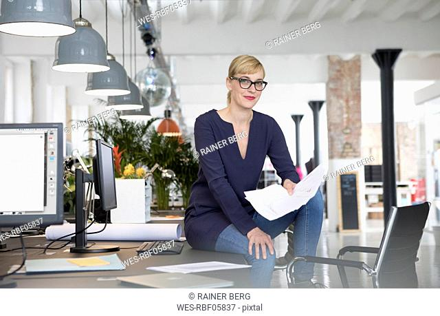 Businesswoman sitting on desk, holding papers