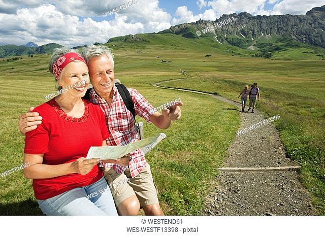 Italy, Seiseralm, Senior couple holding map, smiling, portrait