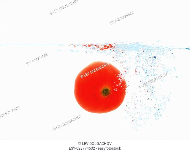 vegetables, food and healthy eating concept - close up of red fresh tomato falling or dipping in water with splash over white background