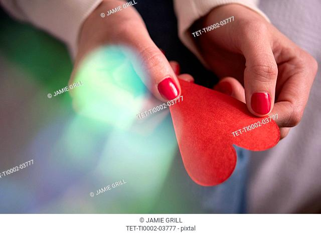 Hands of woman holding red paper heart