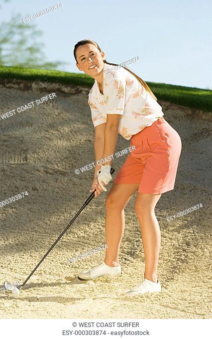 Female golfer hitting ball from sand trap