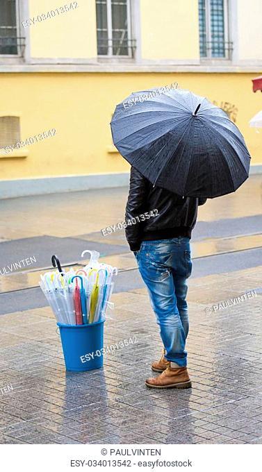 Man stood in rain on street selling umbrellas