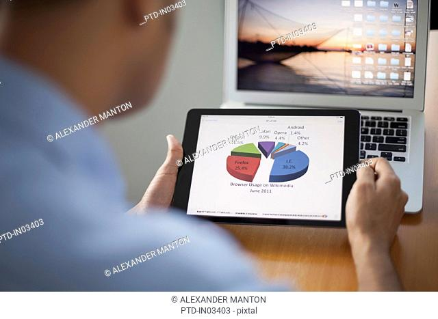 Singapore, Businessman looking at pie chart on digital tablet