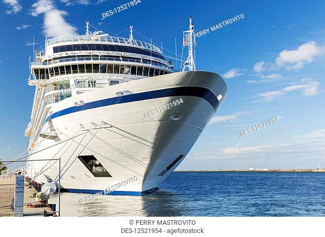 White and blue cruise ship moored at dock, Port of Warnemunde; Rostock, Germany