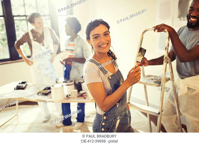 Portrait smiling, confident woman painting living room with friends