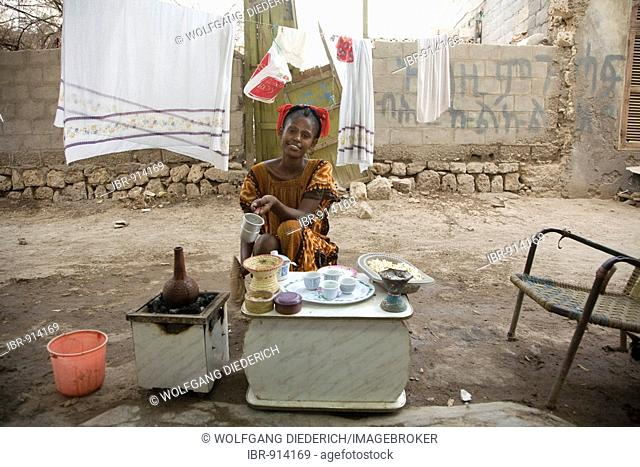 Young woman, 20-25 years old, preparing coffee in the open air during high-summer temperatures of 45°C, Red Sea, Massawa, Eritrea, Africa