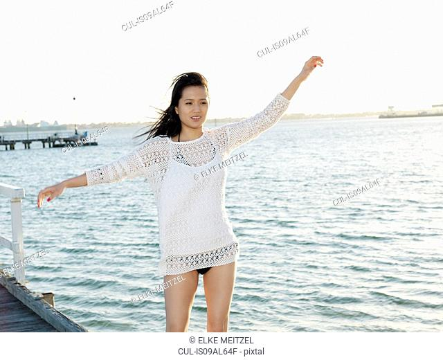 Portrait of young woman on beach with arms raised, Port Melbourne, Melbourne, Victoria, Australia