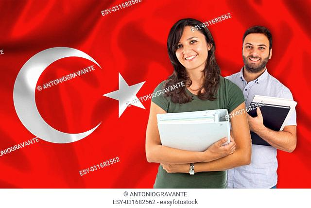 Couple of young students with books over turkish flag