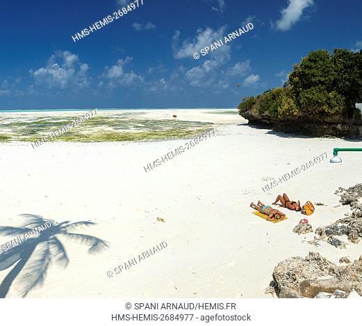 Tanzania, Zanzibar, Jambiani, young foreign women sunbathe on the white sand in front of a luxury hotel