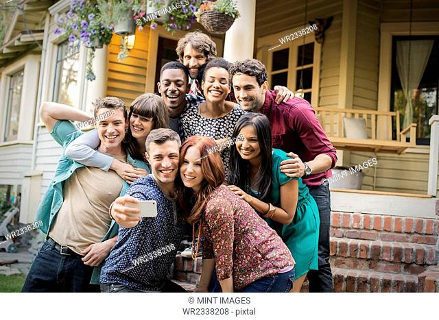 A group of friends posing on the steps of a house porch, taking a group selfy