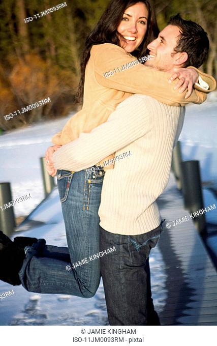 Man picking up woman, laughing