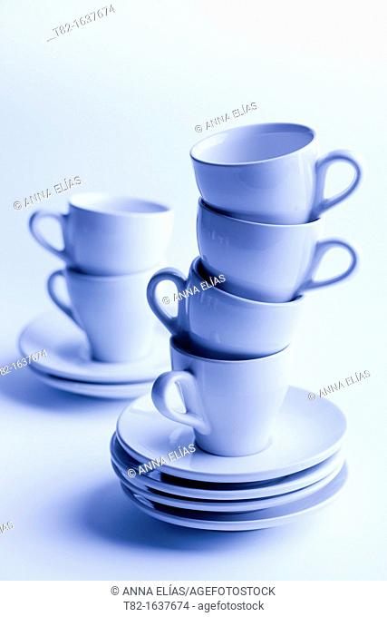 two stacks of cups and saucers for coffee blue on blue background