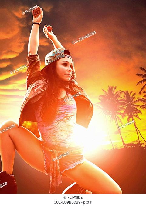 Dancer with arms raised, palm trees at sunset in background