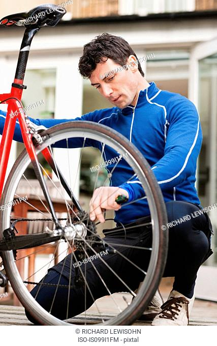Mid adult man adjusting bicycle wheel