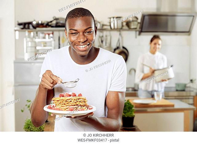 Portrait of young man sprinkling icing sugar on waffles in the kitchen