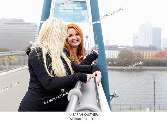 Friends laughing together on a bridge