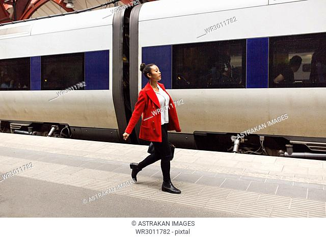 Woman in red coat walking alongside train at station