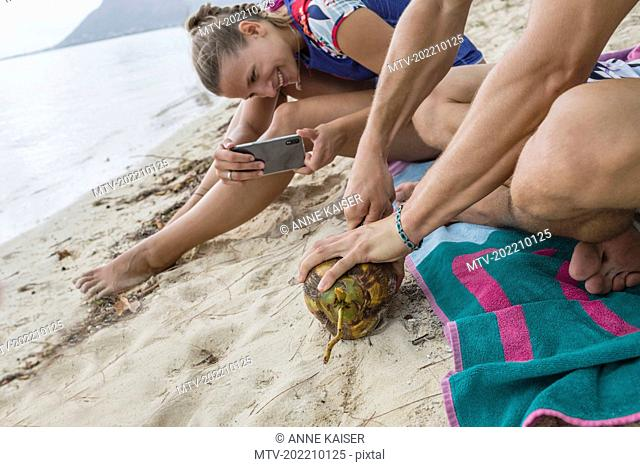 Woman photographing man opening coconut at beach