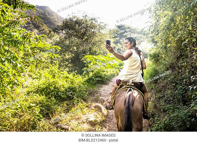 Hispanic woman taking pictures on horseback in jungle