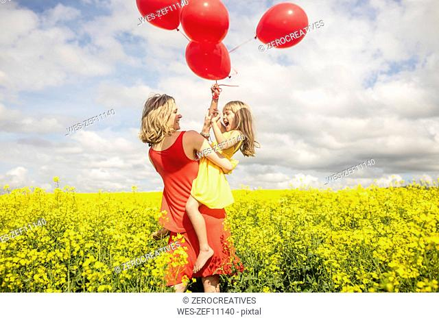 Mother and little daughter having fun with red balloons in rape field