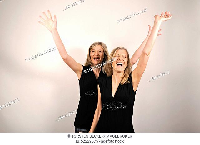 Twin sisters cheering with arms raised
