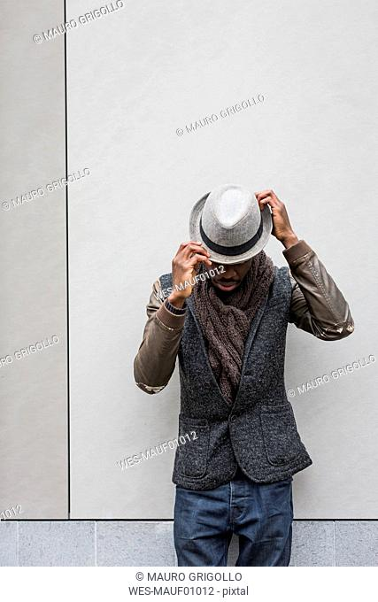 Stylish man putting on hat